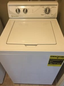 My Speed Queen washer with an energy guide sticker on the front showing eleven dollars of cost per year in electricity.